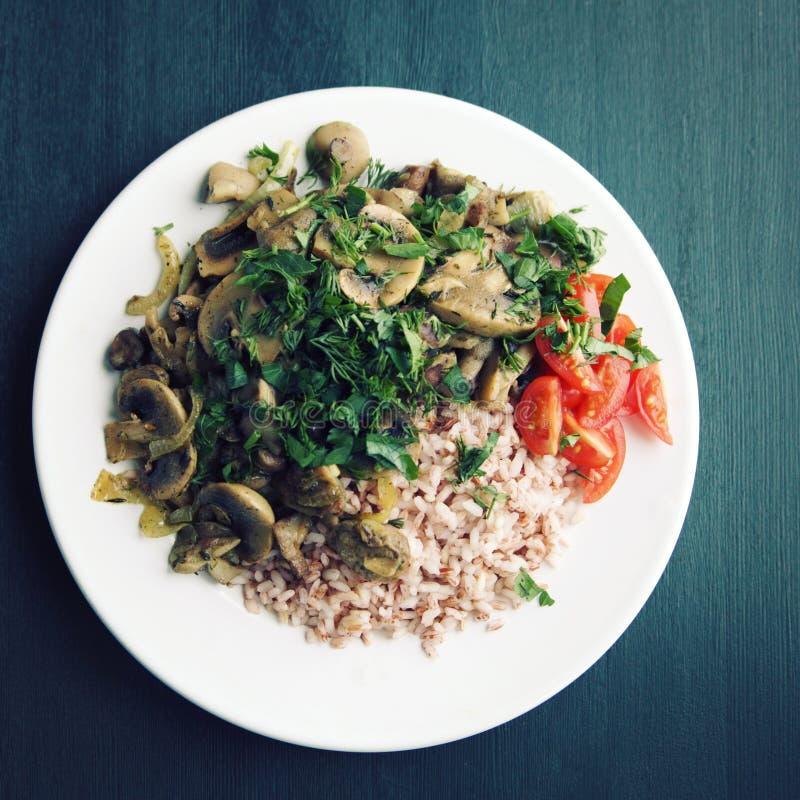 Κόκκινο ρύζι με τα μανιτάρια και τις ντομάτες Πιάτο Vegan στοκ φωτογραφίες