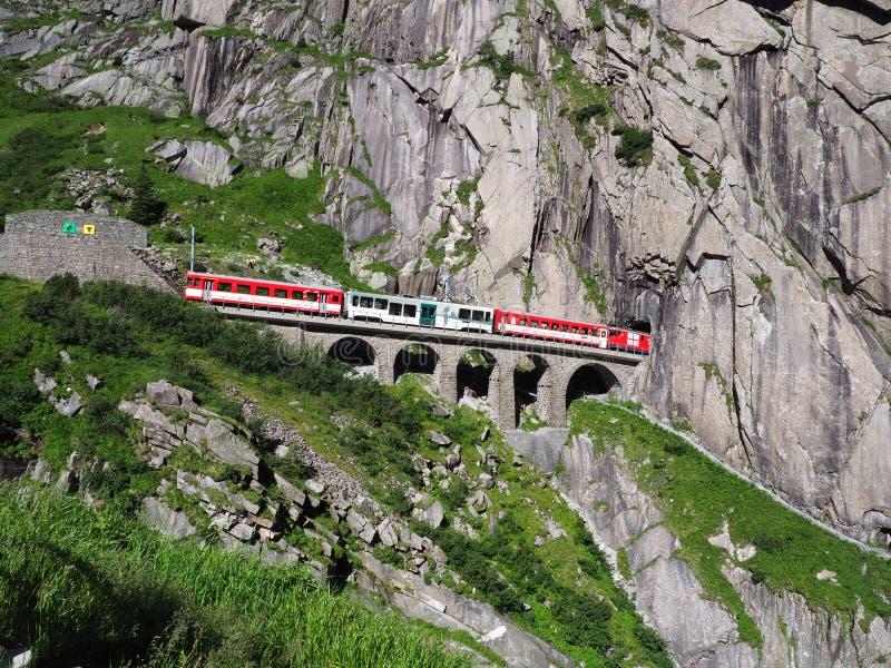 Κόκκινο σαφές τραίνο στη φυσικές πετρώδεις γέφυρα σιδηροδρόμων του ST Gotthard και τη σήραγγα, ελβετικές Άλπεις, ΕΛΒΕΤΊΑ στοκ φωτογραφία
