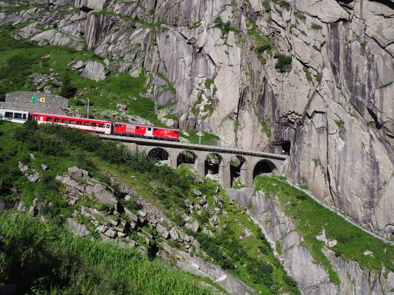 Κόκκινο σαφές τραίνο στη φυσικές πετρώδεις γέφυρα σιδηροδρόμων του ST Gotthard και τη σήραγγα, ελβετικές Άλπεις, ΕΛΒΕΤΊΑ στοκ φωτογραφία με δικαίωμα ελεύθερης χρήσης