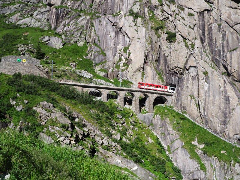 Κόκκινο σαφές τραίνο στη φυσικές πετρώδεις γέφυρα σιδηροδρόμων του ST Gotthard και τη σήραγγα, ελβετικές Άλπεις, ΕΛΒΕΤΊΑ στοκ εικόνες