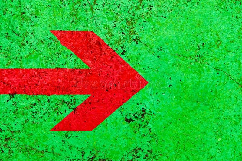 Κόκκινο σημάδι κατεύθυνσης βελών πέρα από το ζωηρό βεραμάν τοίχο πετρών χρώματος με τις ατέλειες και τις ρωγμές στοκ εικόνα