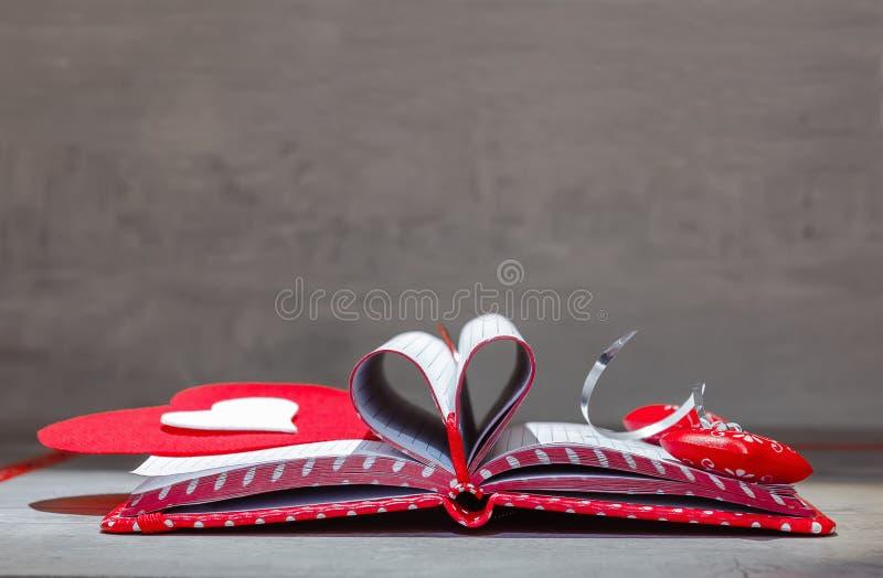 Κόκκινο σημειωματάριο δώρων με τις καρδιές στοκ εικόνες