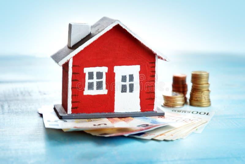 Κόκκινο σπίτι στο ξύλινο υπόβαθρο με τα τραπεζογραμμάτια στοκ εικόνα
