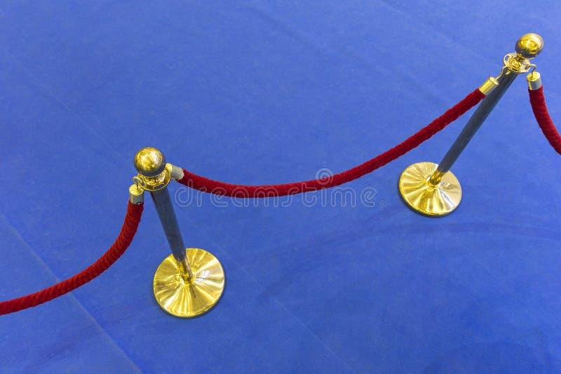 Κόκκινο σχοινί βελούδου και ένας μπλε τάπητας στοκ εικόνες με δικαίωμα ελεύθερης χρήσης