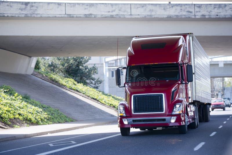 Κόκκινο σύγχρονο ημι φορτηγό με το ρυμουλκό σημαιοφόρων κάτω από τη γέφυρα στοκ φωτογραφία με δικαίωμα ελεύθερης χρήσης
