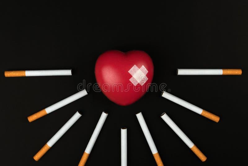 Κόκκινο σύμβολο καρδιών με το συγκολλητικό ασβεστοκονίαμα μεταξύ των τσιγάρων στοκ φωτογραφία με δικαίωμα ελεύθερης χρήσης