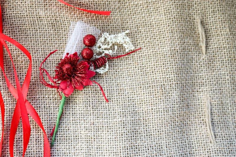 Κόκκινο τεχνητό λουλούδι με τις κόκκινες εορταστικές κορδέλλες σε ένα υπόβαθρο της καφετιάς παλαιάς σύστασης υφάσματος λινού, φυσ στοκ εικόνα