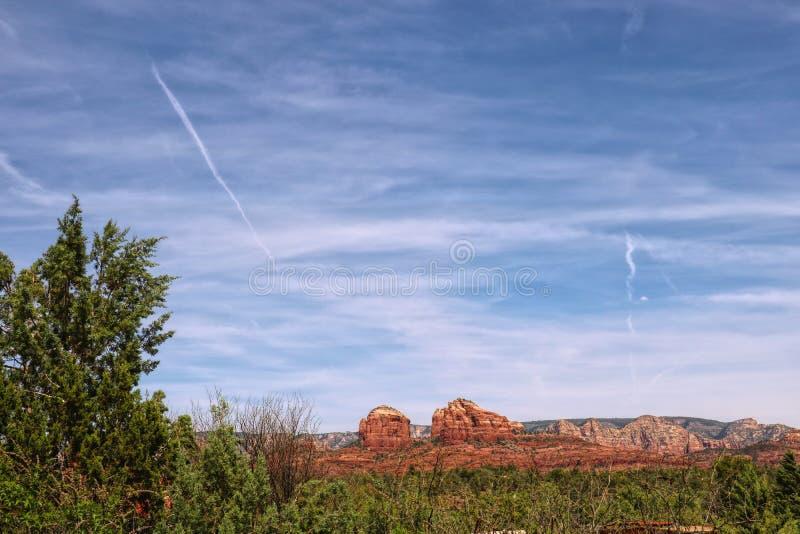 Κόκκινο τοπίο βράχου κάτω από έναν μπλε ουρανό με το σκούπισμα των σύννεφων στοκ φωτογραφία με δικαίωμα ελεύθερης χρήσης