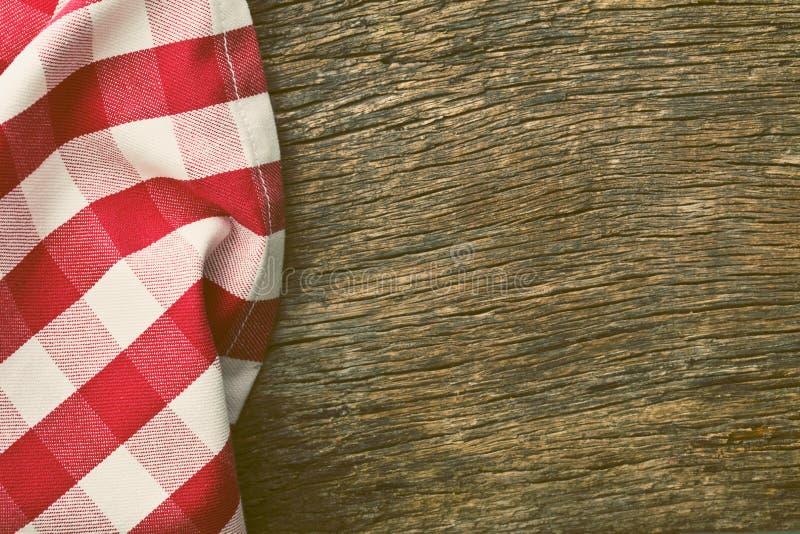 Κόκκινο τραπεζομάντιλο πέρα από τον παλαιό ξύλινο πίνακα στοκ εικόνα