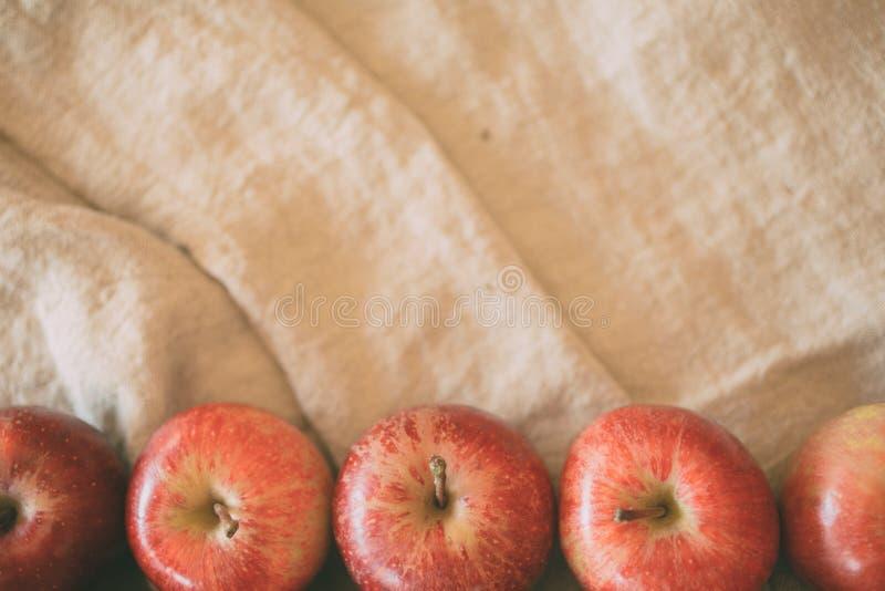 Κόκκινο υπόβαθρο μήλων στο υπόβαθρο λινού με το διάστημα αντιγράφων για το σχέδιο r στοκ φωτογραφίες