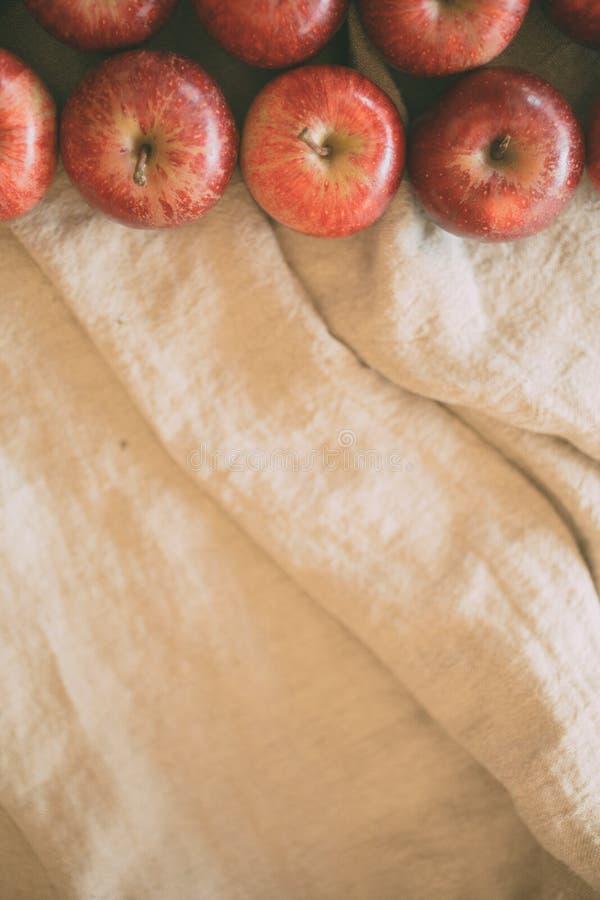 Κόκκινο υπόβαθρο μήλων στο υπόβαθρο λινού με το διάστημα αντιγράφων για το σχέδιο r στοκ εικόνες