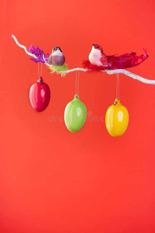 Κόκκινο υπόβαθρο Πάσχας ή άνοιξη - πουλιά και αυγά σε έναν κλαδίσκο στοκ εικόνα με δικαίωμα ελεύθερης χρήσης