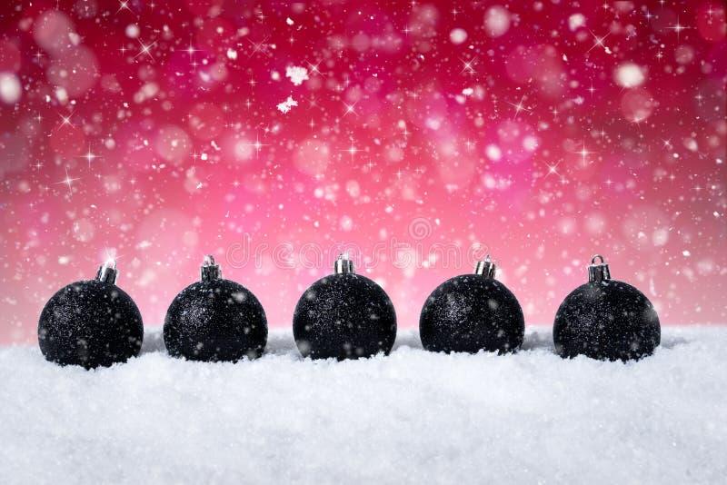 Κόκκινο υπόβαθρο Χριστουγέννων - διακοσμημένες μαύρες σφαίρες στο χιόνι με snowflakes και τα αστέρια στοκ εικόνες με δικαίωμα ελεύθερης χρήσης