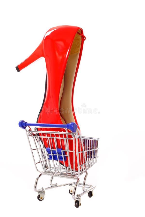 Κόκκινο υψηλό τακούνι σε ένα κάρρο αγορών στοκ εικόνα
