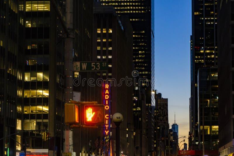 """Κόκκινο φανάρι κυκλοφορίας και Radio City Music Hall στο Μανχάταν Ï""""Î¿ βράδυ στοκ εικόνες"""