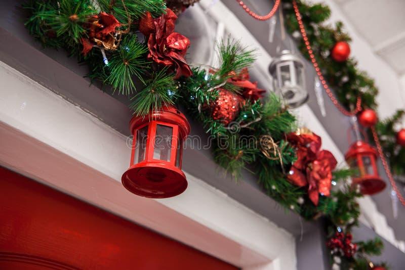 Κόκκινο φανάρι στο διακοσμημένο κλάδο χριστουγεννιάτικων δέντρων Χειμώνας backgroun στοκ φωτογραφία