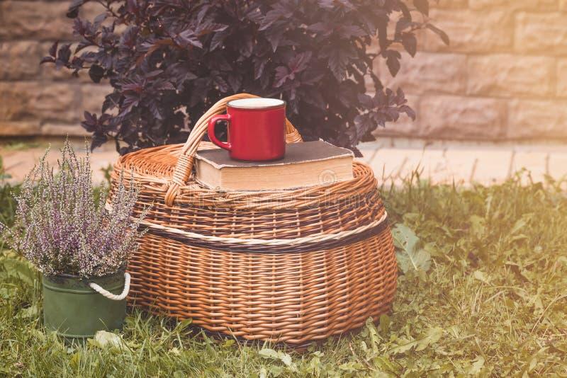Κόκκινο φλυτζάνι καφέ στο καλάθι στον κήπο με την ερείκη σε δοχείο στοκ εικόνα με δικαίωμα ελεύθερης χρήσης