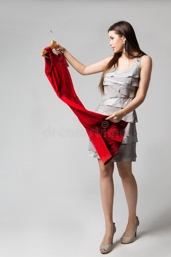 Κόκκινο φόρεμα εκμετάλλευσης γυναικών στην κρεμάστρα, όμορφο κορίτσι που επιλέγει τα ενδύματα, πρότυπο στούντιο μόδας που πυροβολ στοκ εικόνα με δικαίωμα ελεύθερης χρήσης