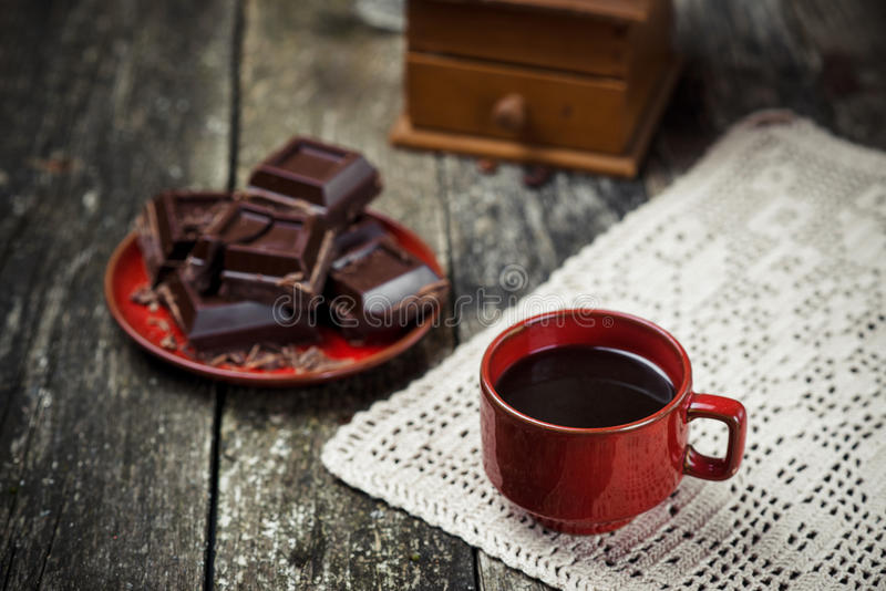 Κόκκινο φλυτζάνι καφέ, κομμάτια της σοκολάτας στο ξύλινο επιτραπέζιο υπόβαθρο βαμμένος Εκλεκτική εστίαση στοκ εικόνες
