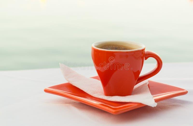 Κόκκινο φλυτζάνι καφέ με μια άποψη της θάλασσας στοκ φωτογραφία