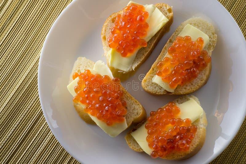 Κόκκινο χαβιάρι στο ψωμί και βουτύρου κινηματογράφηση σε πρώτο πλάνο, τέσσερα σάντουιτς στο άσπρο πιάτο επάνω από την όψη στοκ εικόνα με δικαίωμα ελεύθερης χρήσης