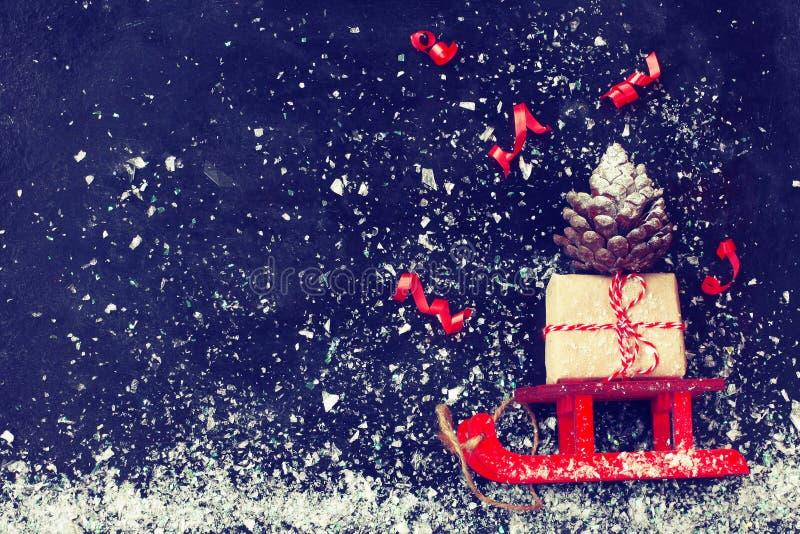Κόκκινο Χριστουγέννων κιβώτιο δώρων ελκήθρων φέρνοντας, κώνος πεύκων, ταινία στο β στοκ φωτογραφίες με δικαίωμα ελεύθερης χρήσης