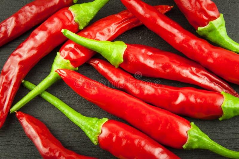 Κόκκινο ψυχρό πιπέρι στο ξύλινο μαύρο υπόβαθρο Κόκκινος - καυτά πιπέρια τσίλι Εσωτερικό έγκαυμα τσίλι καλλιέργειας πρόσθετο καυτό στοκ εικόνες