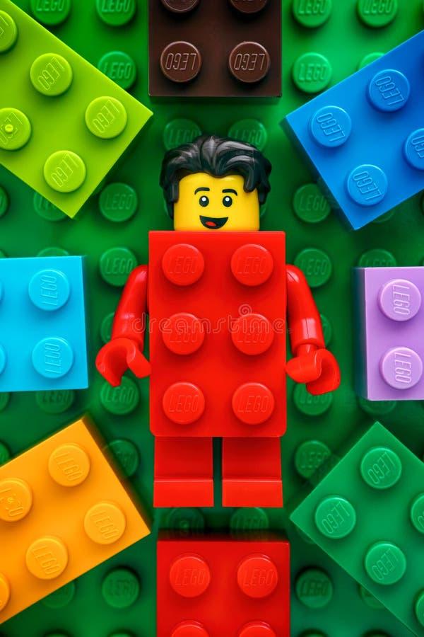 Κόκκινο minifigure τύπων τούβλου κοστουμιών Lego στο πράσινο baseplate υπόβαθρο στοκ φωτογραφία με δικαίωμα ελεύθερης χρήσης