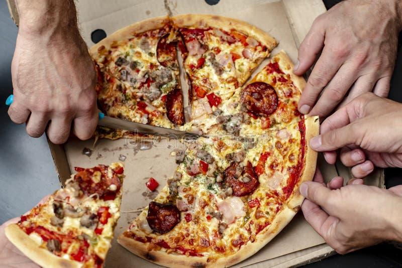 Κόμμα σπιτιών Το ανθρώπινο χέρι κόβει την πίτσα, και οι φίλοι αρπάζουν ένα κομμάτι Υπερυψωμένη όψη στοκ εικόνα