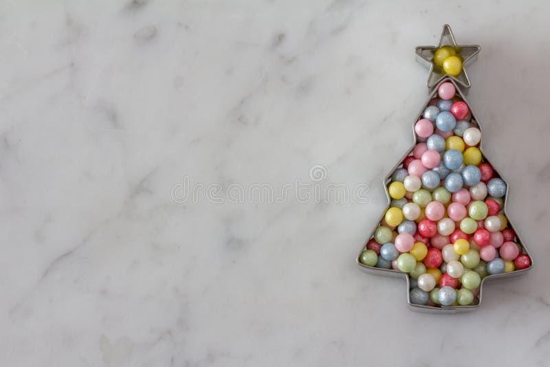 Κόπτης μπισκότων χριστουγεννιάτικων δέντρων με τα μαργαριτάρια ζάχαρης στοκ φωτογραφίες με δικαίωμα ελεύθερης χρήσης