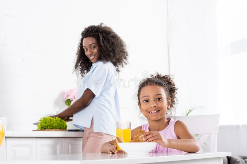 κόρη αφροαμερικάνων με το χυμό από πορτοκάλι και μπισκότα στην κουζίνα στοκ εικόνες