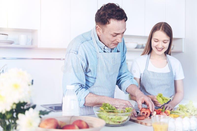 Κόρη και μπαμπάς που απολαμβάνουν να μαγειρεψει από κοινού στοκ εικόνες
