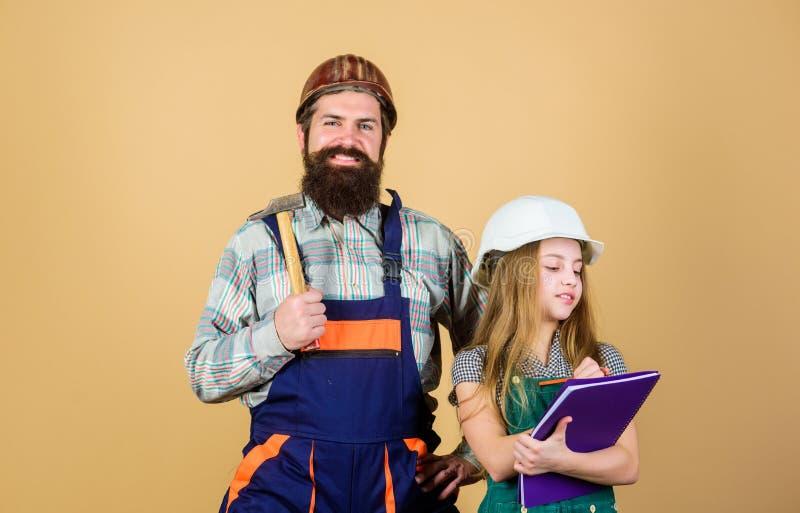 κόρη και πατέρας που επισκευάζουν μαζί στο εργαστήριο πατρότητα Γενειοφόρο άτομο με το μικρό κορίτσι Εκπαίδευση εφαρμοσμένης μηχα στοκ εικόνα