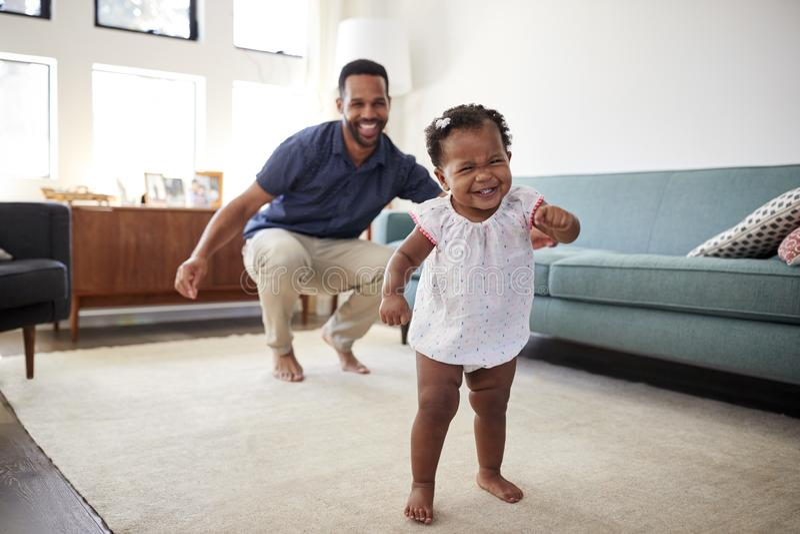 Κόρη μωρών που χορεύει με τον πατέρα στο σαλόνι στο σπίτι στοκ εικόνα