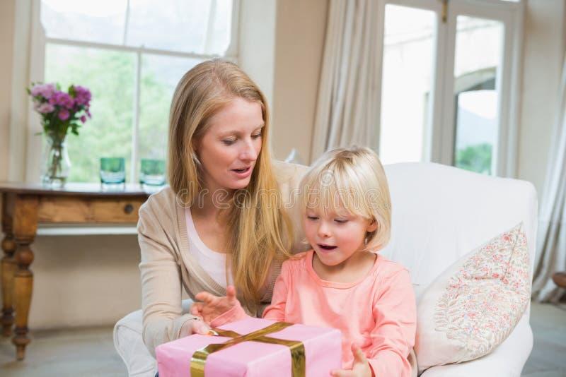 Κόρη που ανοίγει ένα παρόν από το mum στοκ εικόνα