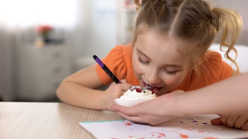 Κόρη που δοκιμάζει το γλυκό επιδόρπιο από το χέρι μητέρων, ανθυγειινό πρόχειρο φαγητό, σχεδιασμός στοκ εικόνες