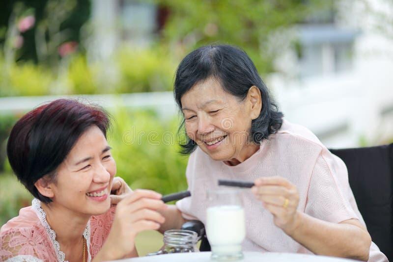 Κόρη που φροντίζει για την ηλικιωμένη ασιατική γυναίκα, σοκολάτα επιλογής στοκ φωτογραφία