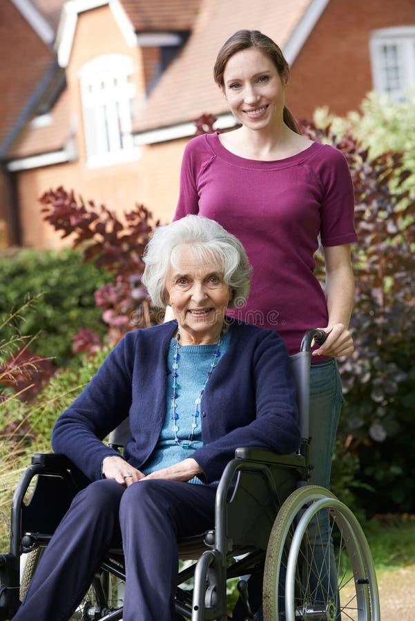 Κόρη που ωθεί την ανώτερη μητέρα στην αναπηρική καρέκλα στοκ εικόνες