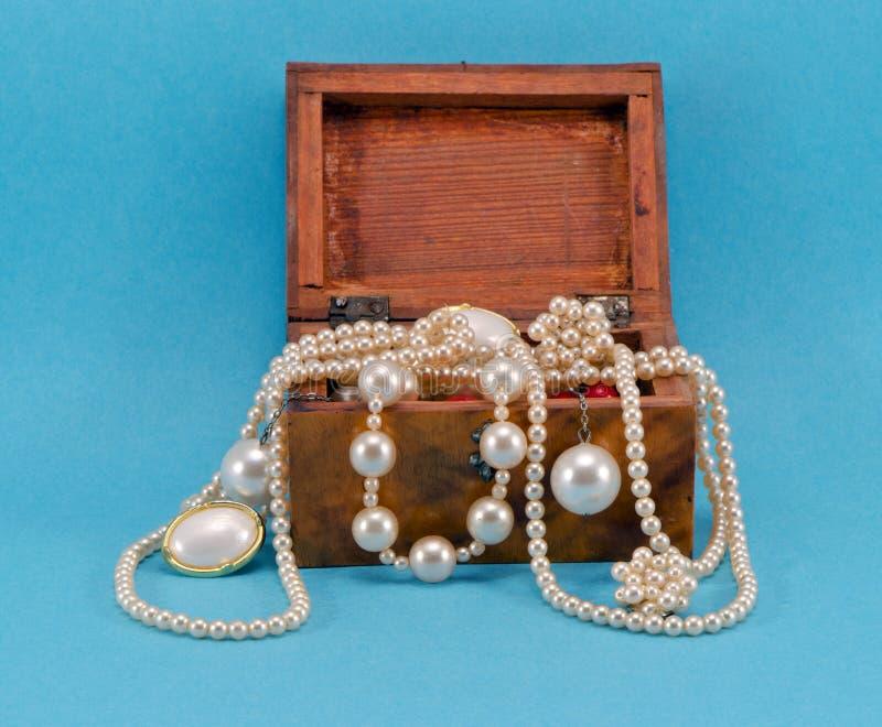 Κόσμημα μαργαριταριών στο αναδρομικό ξύλινο κιβώτιο στο μπλε στοκ εικόνες με δικαίωμα ελεύθερης χρήσης