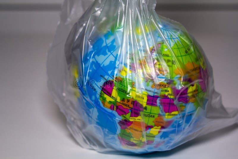 Κόσμος που τυλίγεται στο πλαστικό πλαστική έννοια ρύπανσης στοκ φωτογραφία
