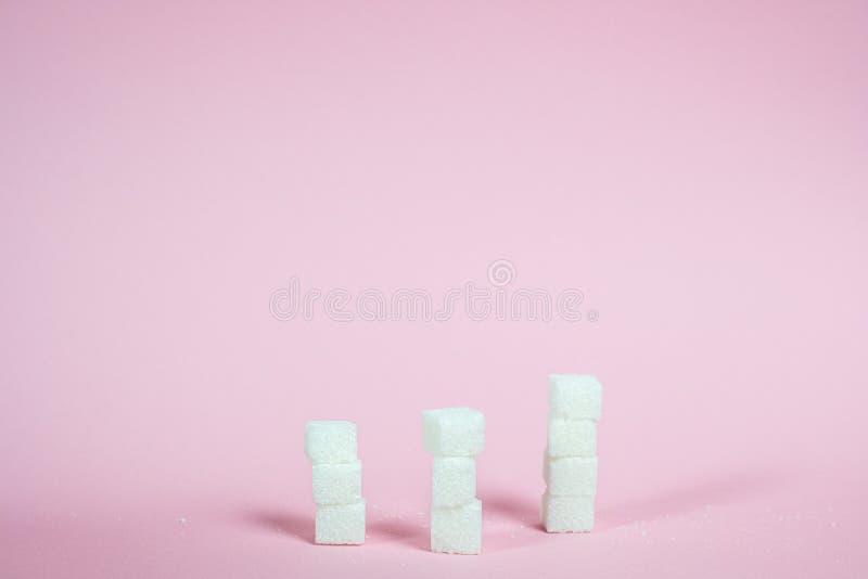 Κύβοι άσπρης ζάχαρης σε ένα ρόδινο υπόβαθρο στοκ φωτογραφία
