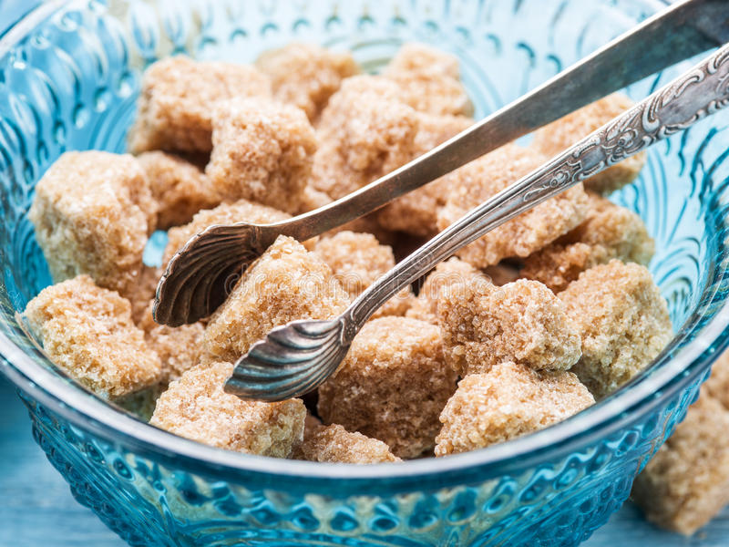 Κύβοι ζάχαρης καλάμων στο ντεμοντέ πιάτο γυαλιού στοκ φωτογραφίες