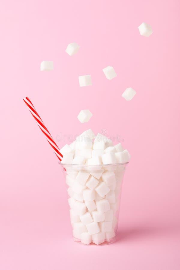Κύβοι ζάχαρης που περιέρχονται στο γυαλί στη ρόδινη έννοια διατροφής υποβάθρου ανθυγειινή στοκ φωτογραφίες με δικαίωμα ελεύθερης χρήσης