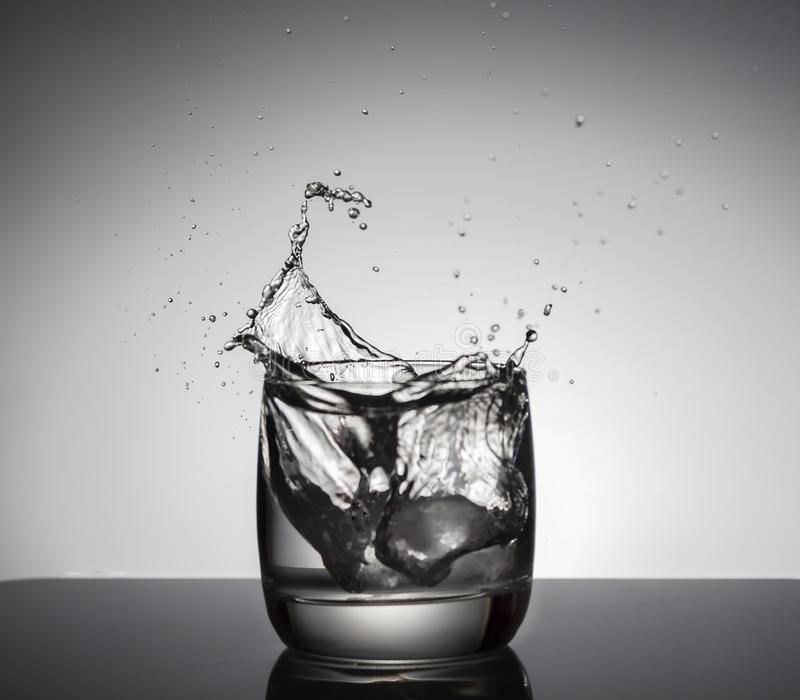 Κύβοι πάγου που καταβρέχουν στο ποτήρι του νερού στοκ εικόνες με δικαίωμα ελεύθερης χρήσης