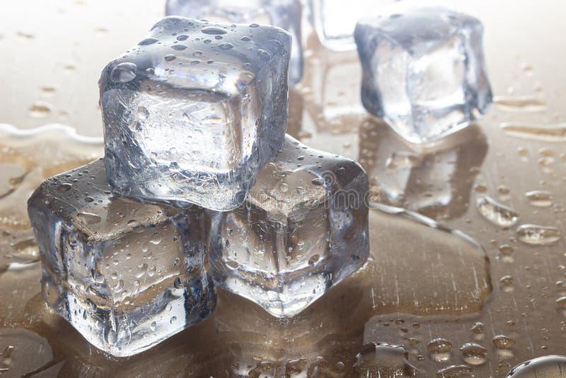 Κύβοι πάγου στο καφετί υπόβαθρο στοκ φωτογραφίες
