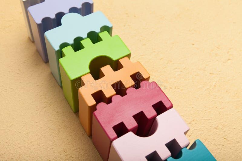 Κύβοι των διαφορετικών μορφών σε μια σειρά, έννοια χτισίματος ομάδας στοκ εικόνα