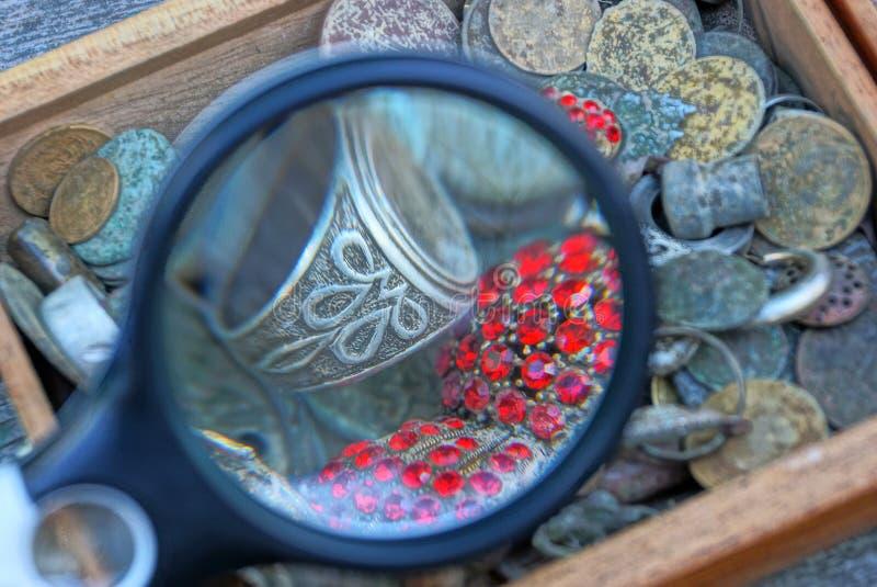 Κύκλος πιό magnifier πέρα από έναν σωρό των παλαιών κοσμημάτων σε ένα κιβώτιο στοκ εικόνες