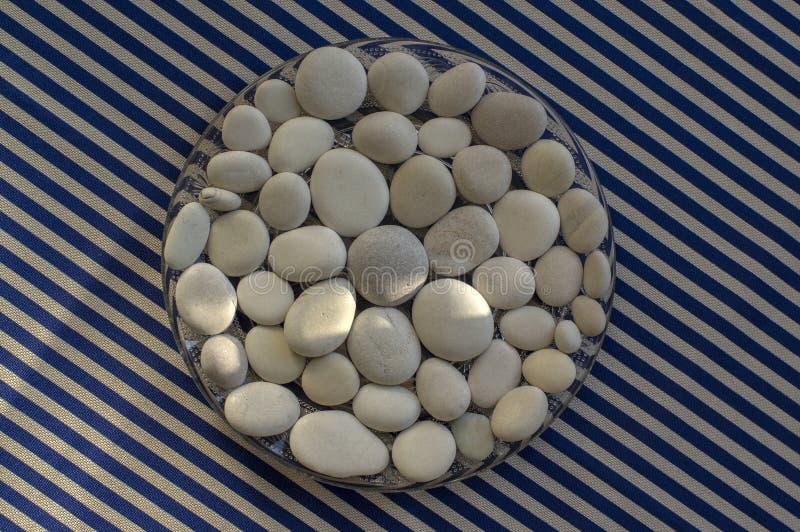 Κύκλος που αποτελείται από τις άσπρες και γκρίζες πέτρες, υπόβαθρο mandala χαλικιών στο μπλε άσπρο ριγωτό υπόβαθρο στο φως της ημ στοκ εικόνα με δικαίωμα ελεύθερης χρήσης