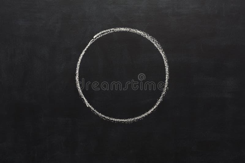 Κύκλος που επισύρεται την προσοχή με την κιμωλία στον πίνακα στοκ εικόνα
