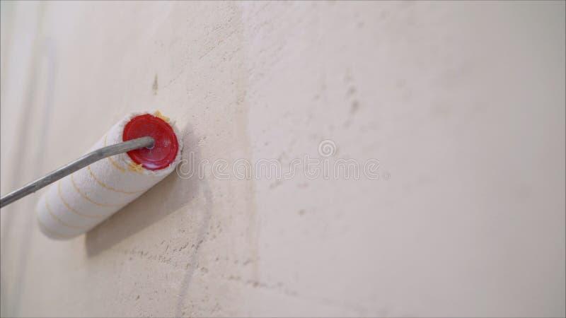 Κύλινδρος χρωμάτων τοίχων Ζωγραφική βουρτσών κυλίνδρων, ζωγραφική εργαζομένων στη βούρτσα κυλίνδρων για την προστασία στοκ εικόνα με δικαίωμα ελεύθερης χρήσης